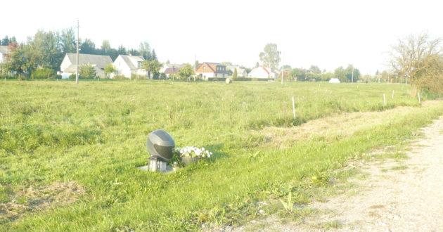 Šalia kelio paminklas žuvusiam motociklininkui- šalmas iš akmens.